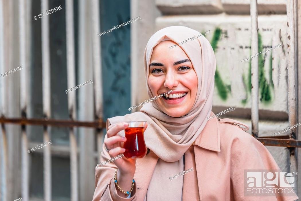 Photo de stock: Beautiful Muslim woman in headscarf and fashionable modern clothes drinks Traditional Turkish drinks tea. Modern Muslim women lifestyle or travel tourist.