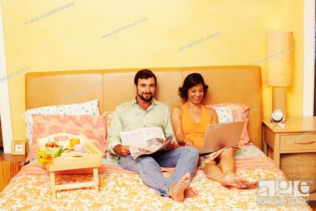 Stock Photo: Portrait of a mature man sitting on the bed with a mature woman using a laptop beside him.