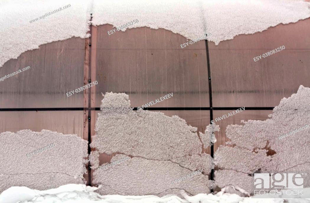 Stock Photo: Plastic private greenhouse in snow. Seasonal background.