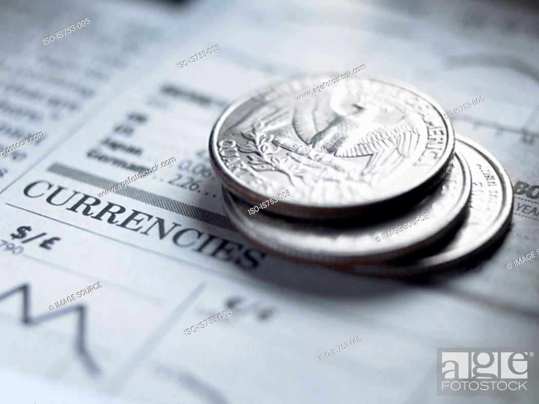 Stock Photo: Quarters on a newspaper.
