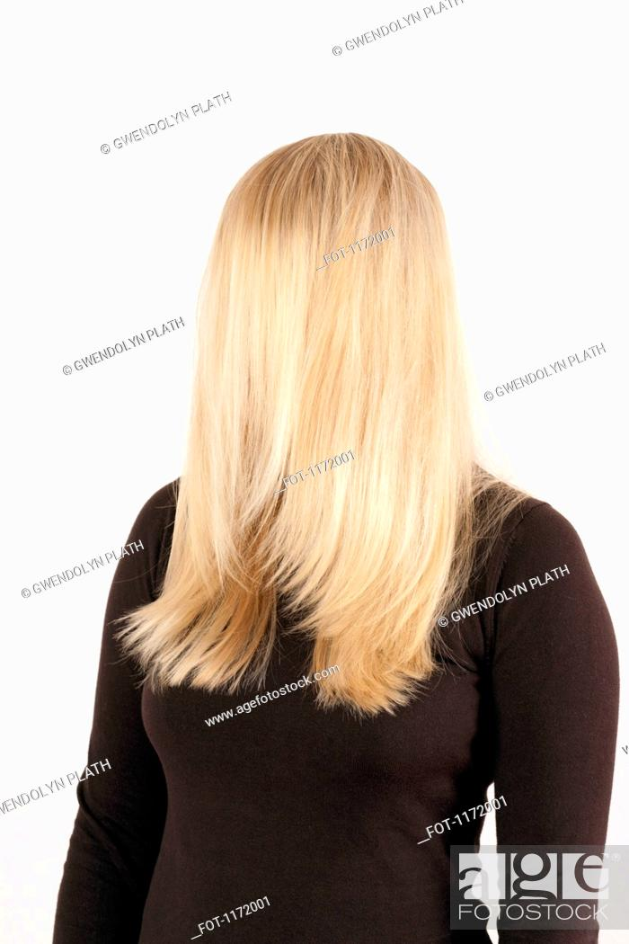 Stock Photo: A woman standing with her long, blond hair combed forward covering her face.