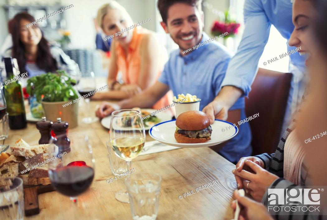 Stock Photo: Waiter serving slider hamburger to woman dining with friends at restaurant table.
