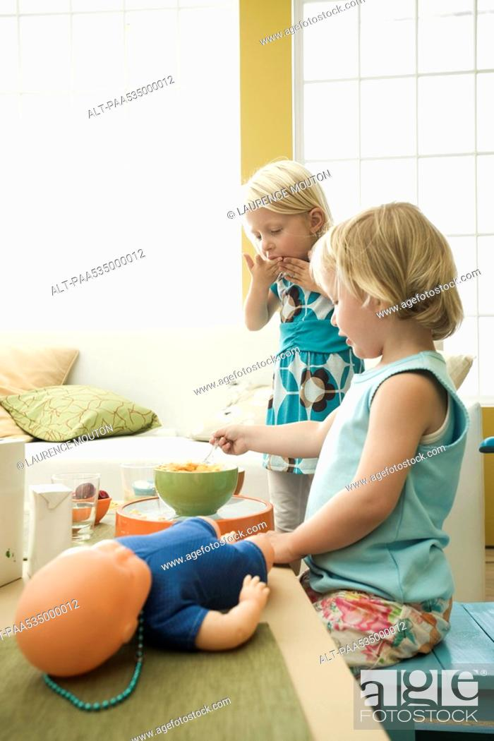 Stock Photo: Little girls eating breakfast at messy table.