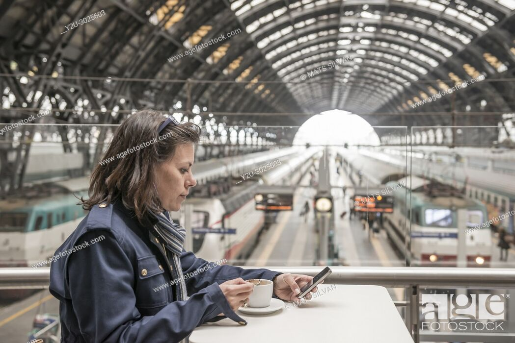 Stock Photo: Woman Sitting in a Bar with a Cup of Coffee and Using a Smart Phone in a Train Station in Milan and Waiting in Lombardy, Italy.