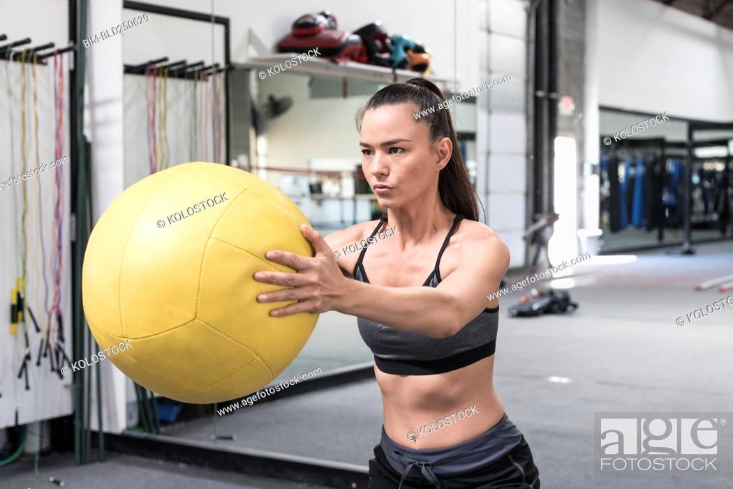Stock Photo: Mixed race woman lifting heavy ball in gymnasium.