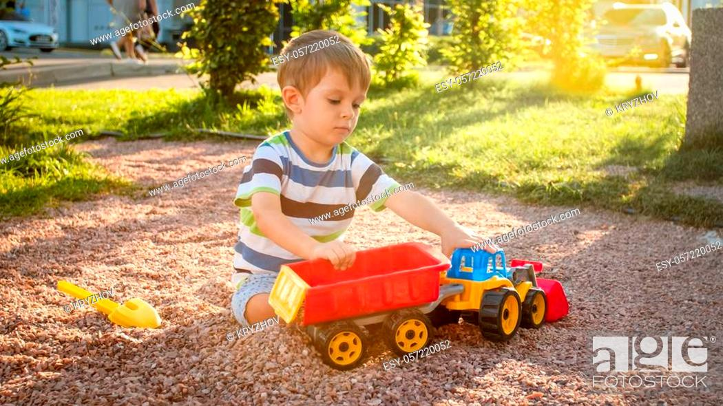 Stock Photo: Closeup portrait of happy smiling 3 years old child boy digging sand on playground with toy plastic truck or excavator. Child palying and having fun at park at.