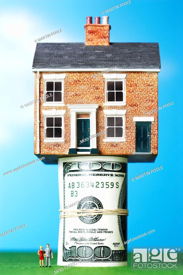 Stock Photo: Model house on roll of $100 notes.