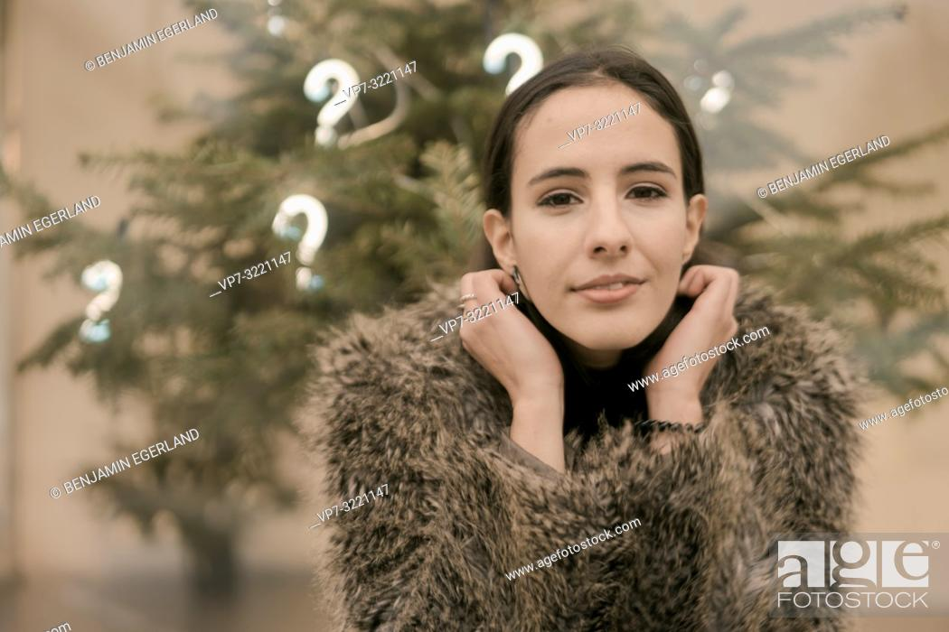 Stock Photo: confident woman in front Christmas tree with lights of question marks, in Munich, Germany.