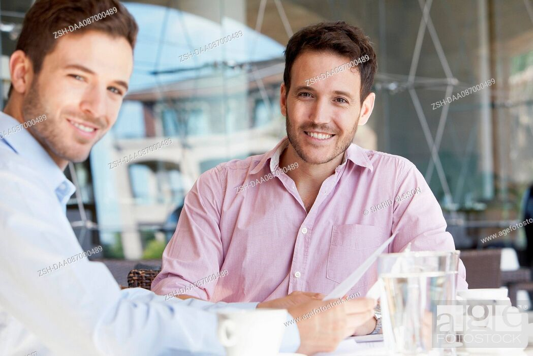 Stock Photo: Insurance agent discussing contract with client over coffee.