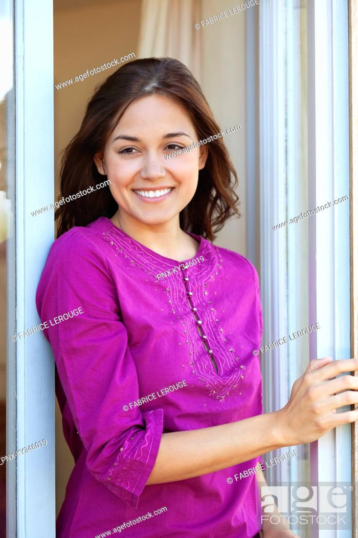 Stock Photo: Woman standing at a window and smiling.