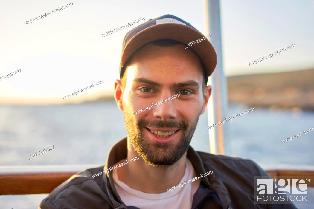 Stock Photo: Portrait of happy smiling young French student man with cap during sunset in Malta, Europe.