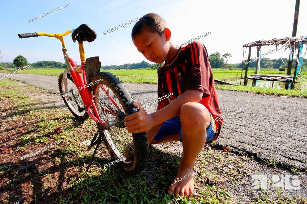 Stock Photo: Boy and his bicycle, kuching, sarawak, malaysia.