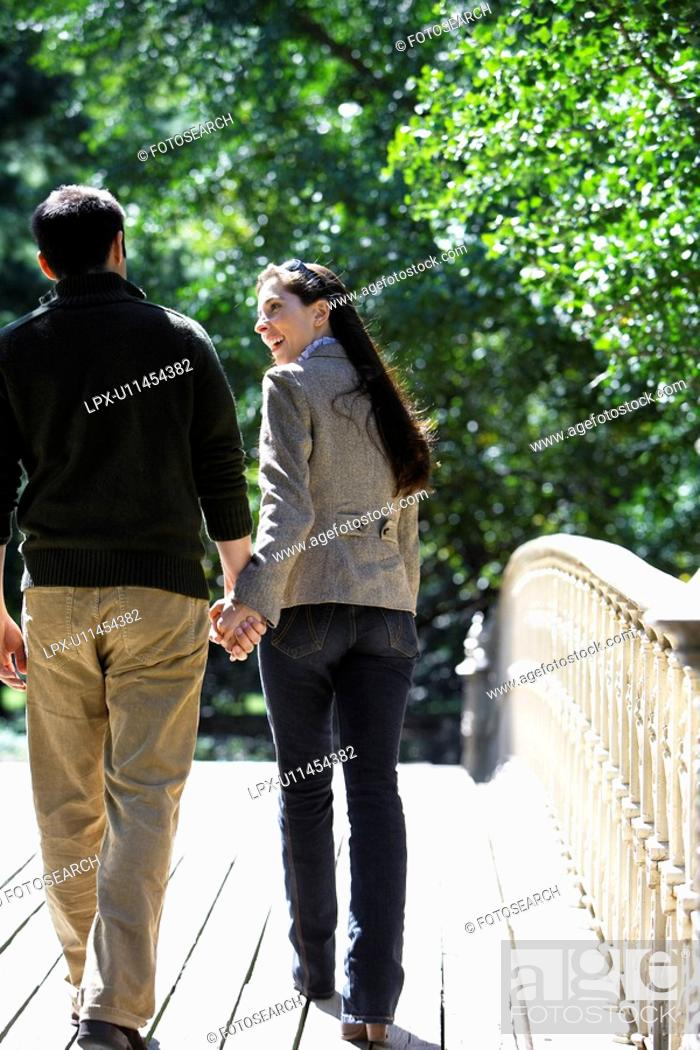 Stock Photo: Couple walking on footbridge rear view.
