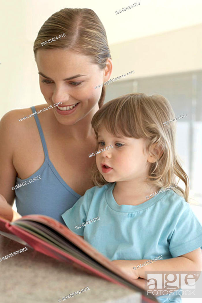 Stock Photo: Mother helping her daughter to read.