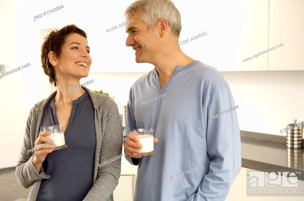Stock Photo: Mature man and a mid adult woman holding glasses of milk.