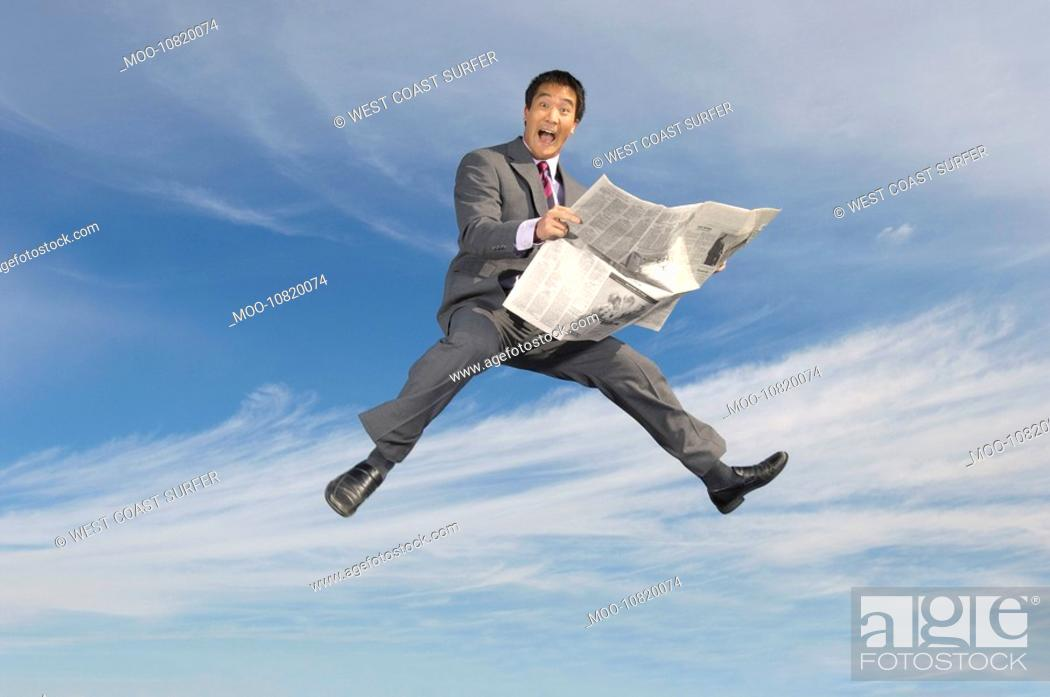 Stock Photo: Business man reading newspaper mid-air outdoors.