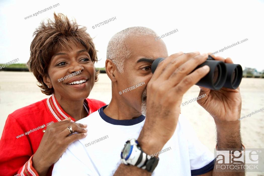 Stock Photo: Couple using binoculars at beach.