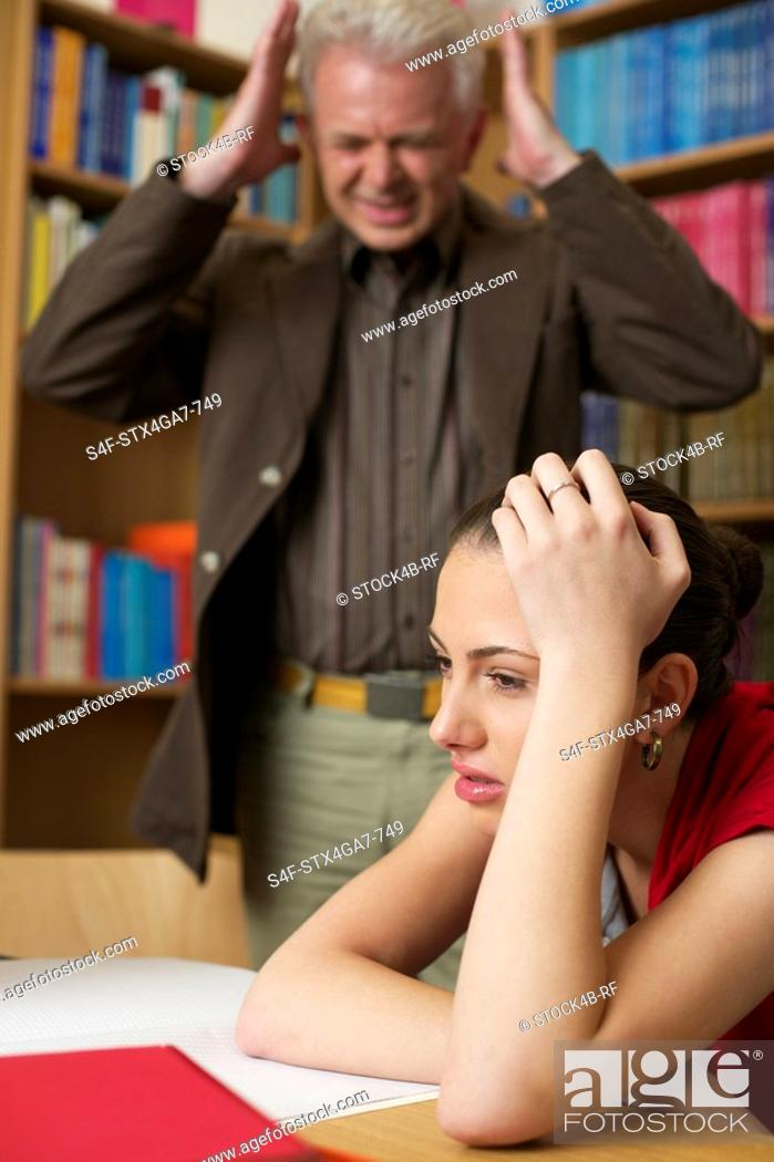 Stock Photo: Despaired female student and frustrated professor in background.