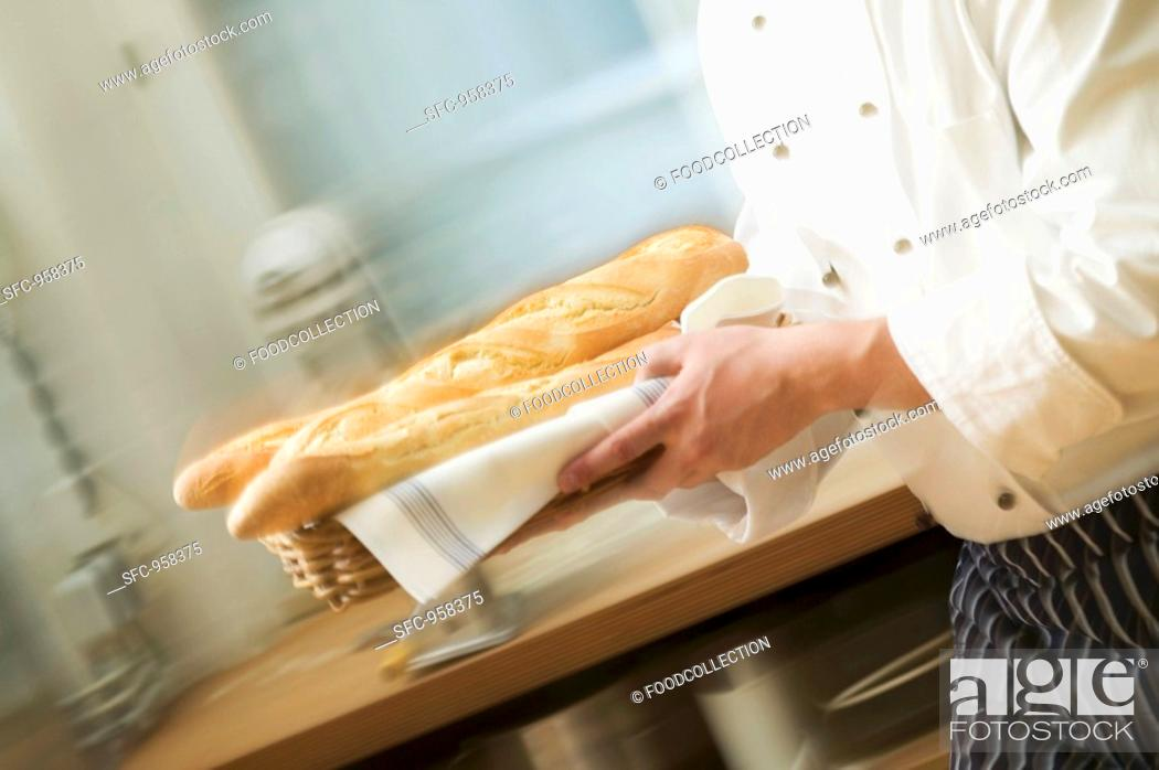 Stock Photo: Chef hurrying through kitchen with baguettes.