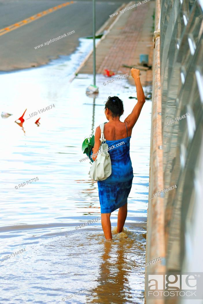 Stock Photo: Woman walking along flooded street in Rio Branco, Acre, Brazil. February 2012.