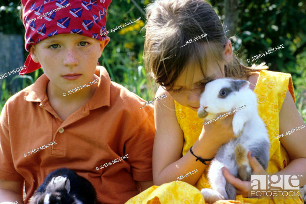 Stock Photo: Two children, a boy and a girl, 5-10 years old, in the garden in summer, holding rabbits, bunnyies in their arms.