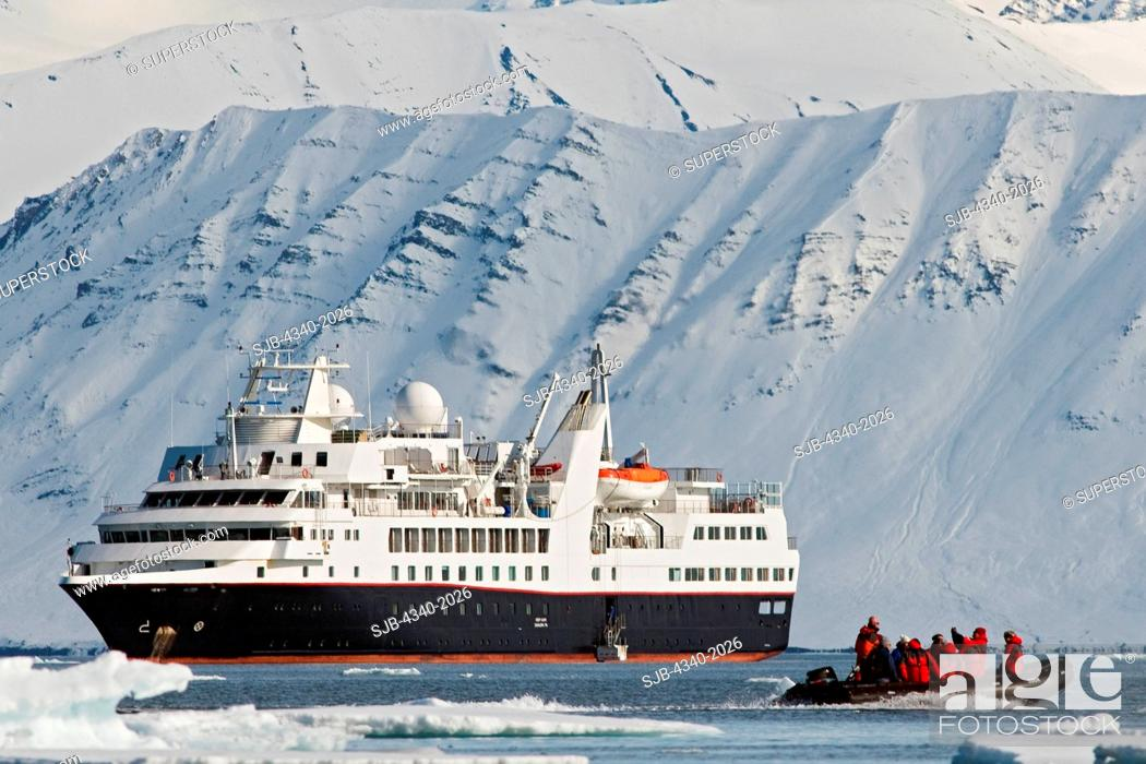 Stock Photo: Zodiacs filled with tourists disembark from a cruise ship to view a polar bear sow and cub resting on Andoyane island, Liefdefjorden, northwest Svalbard, Norway.