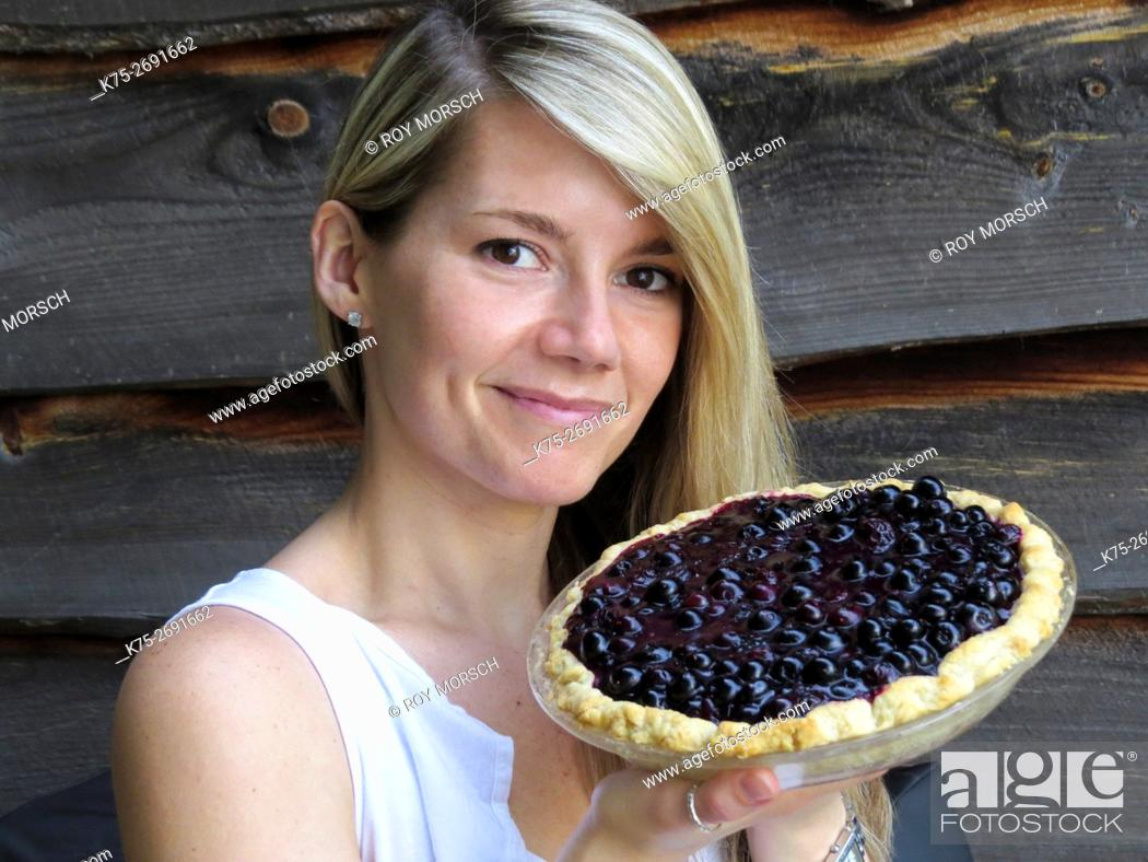 Imagen: Young woman holding homemade blueberry pie.