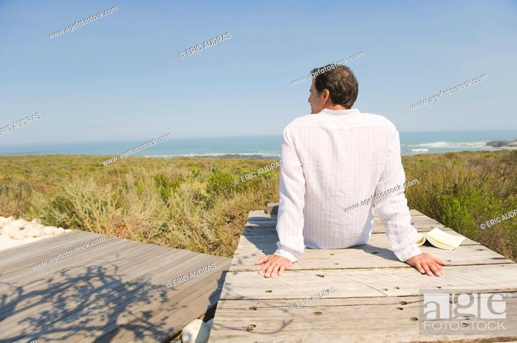 Stock Photo: Rear view of a man sitting on a boardwalk on the beach.