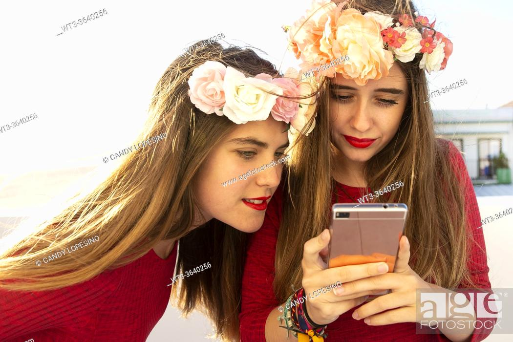 Stock Photo: Two young girls with red dress and long blonde hair and roses looking a selfie.