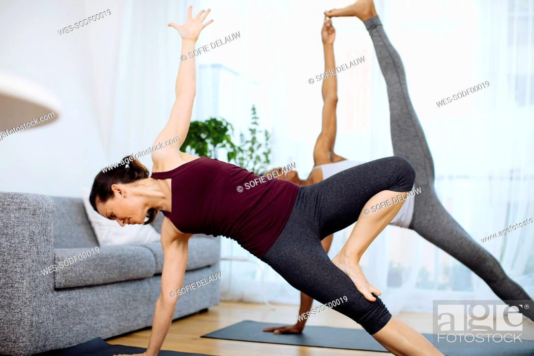 Stock Photo: Two women practicing yoga at home.