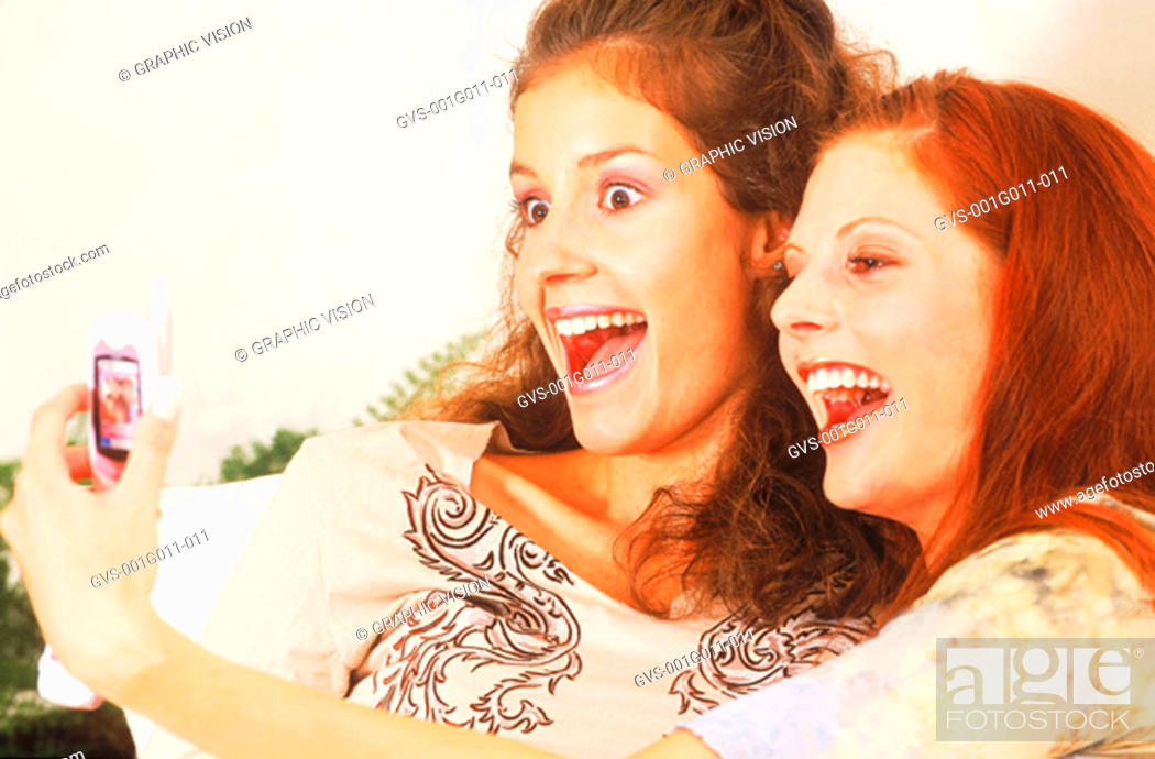 Stock Photo: Young women holding mobile phone and smiling.