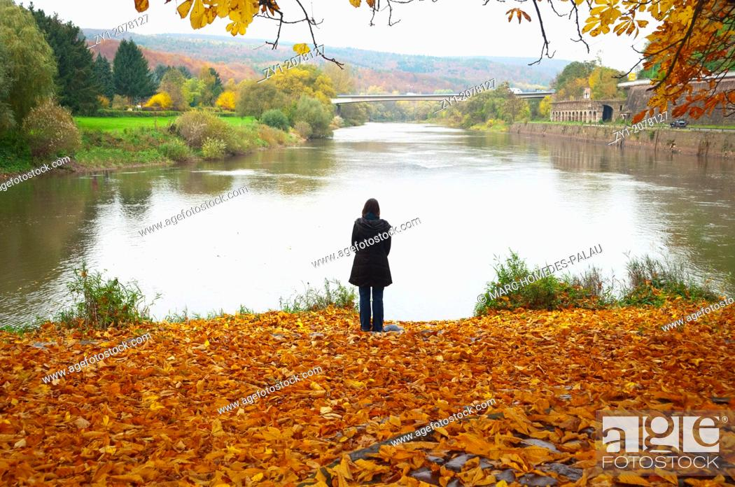 Stock Photo: Autumn scene. Pensive woman at the river in Hannover Münden Germany.