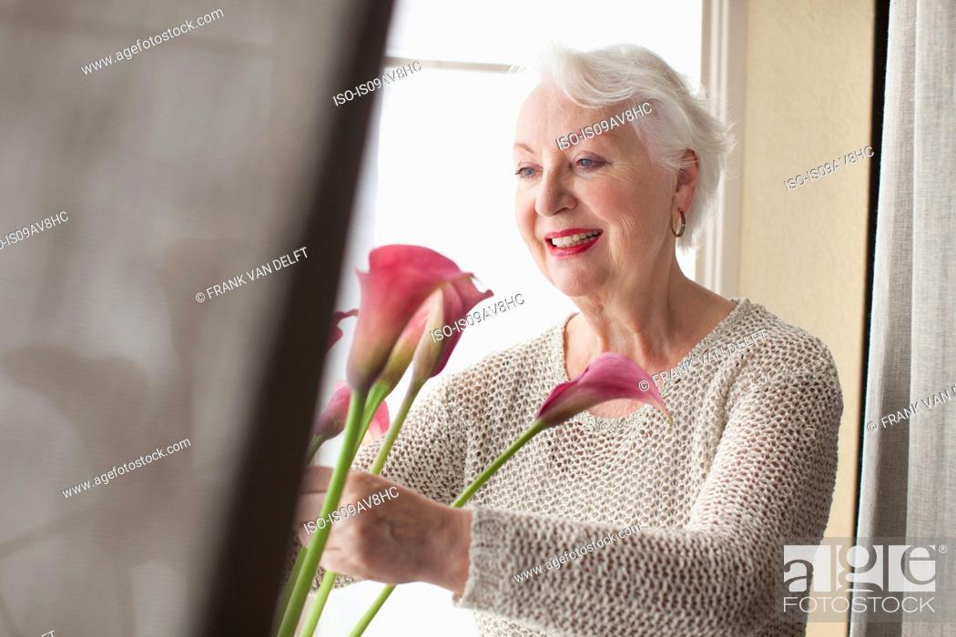 Stock Photo: Senior woman arranging flowers ion window sill.