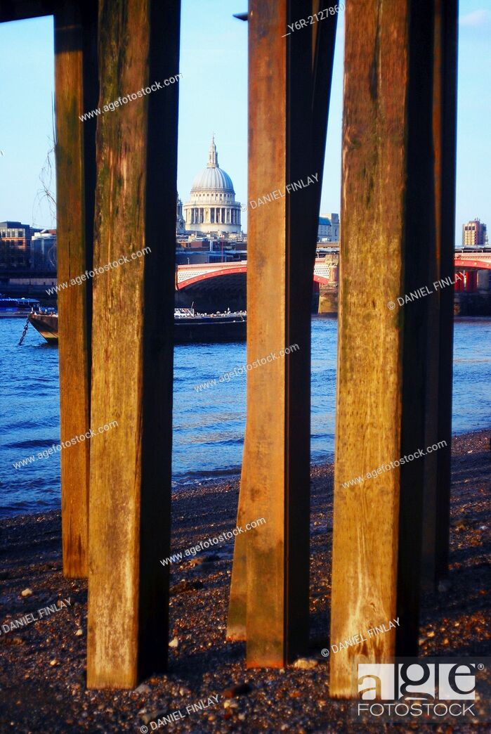 Stock Photo: View across the River Thames to St. Paul's Cathedral at very low tide with the wooden pillars of an old pier in the foreground, in the heart of London, England.