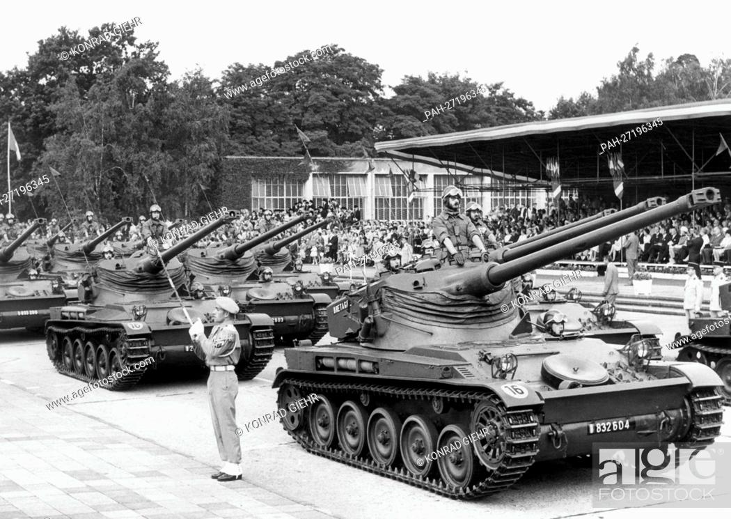 Stock Photo: Tanks roll past the guests and a playing military band in the headquarter of the French army Quartier Napoleon in Berlin during a parade on the occasion of the.