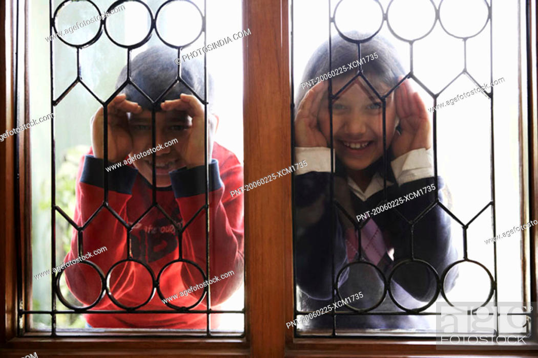Stock Photo: Close-up of two children peeking through a window.