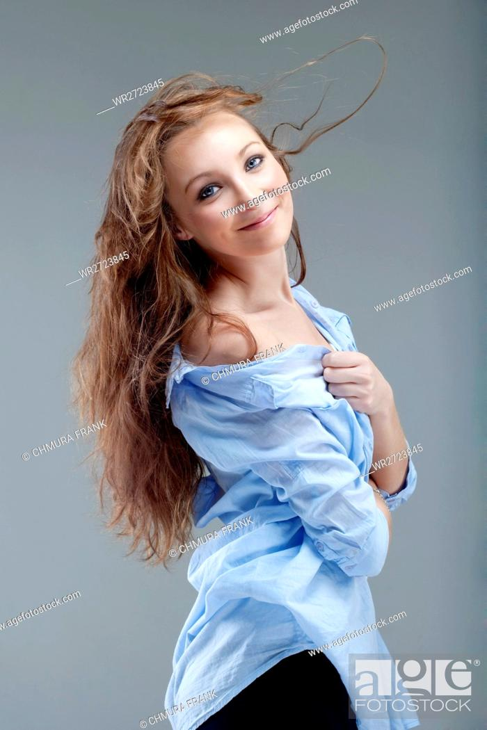Stock Photo: portrait of a young beautiful woman with brown hair smiling - isolated on gray.