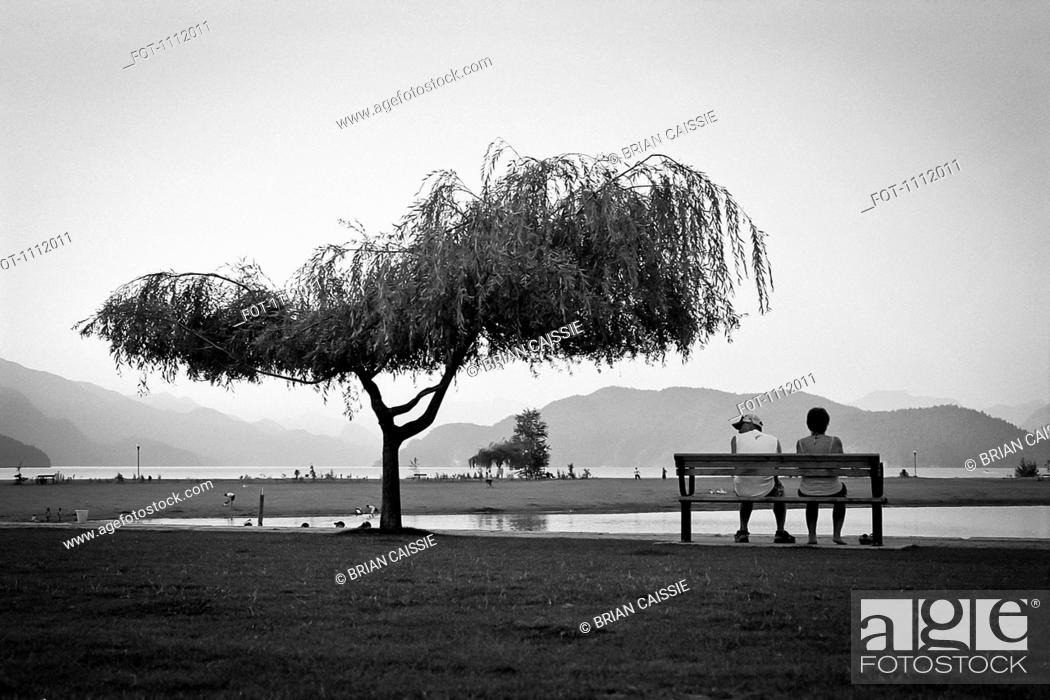 Stock Photo: Two people sitting on a bench, Harrison Hot Springs, British Columbia.