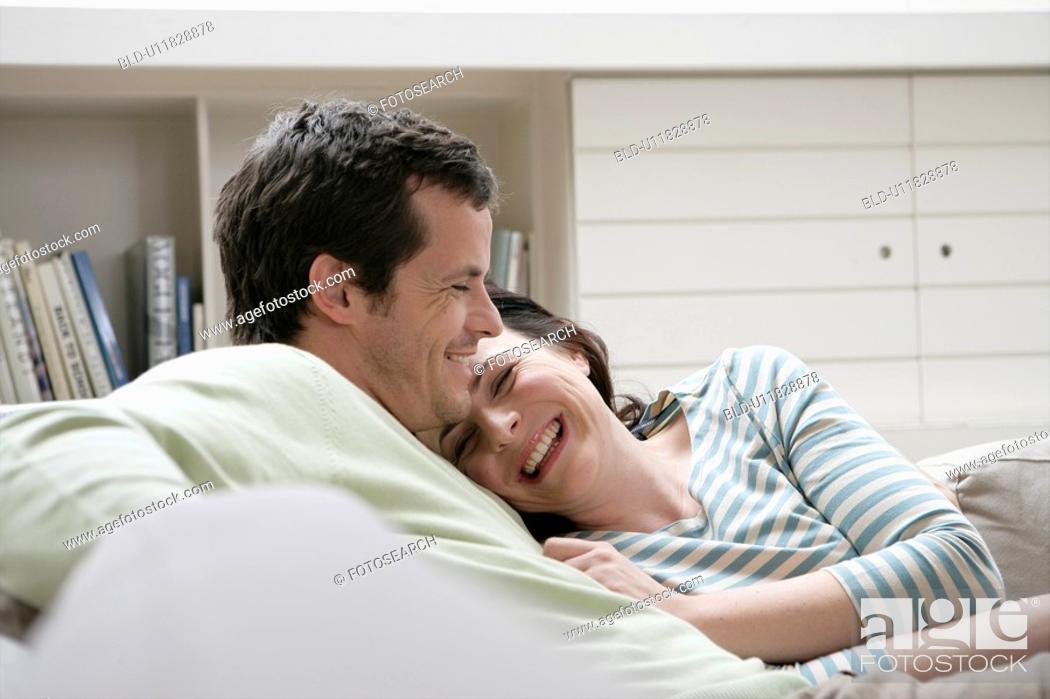 Stock Photo: Mid adult couple sitting on sofa.