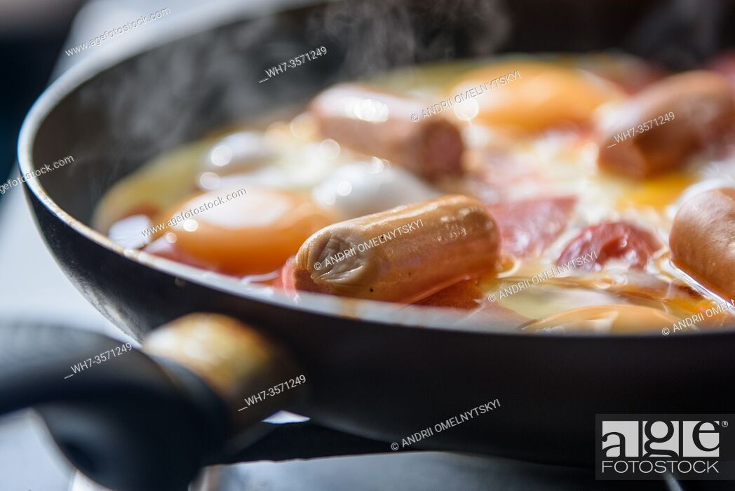 Imagen: fried eggs with sausages and tomatoes on a hot pan, cooking breakfast.