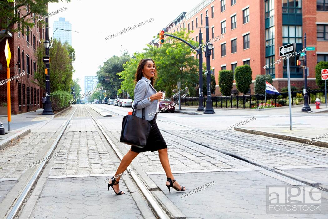 Stock Photo: Businesswoman crossing light rail tracks.