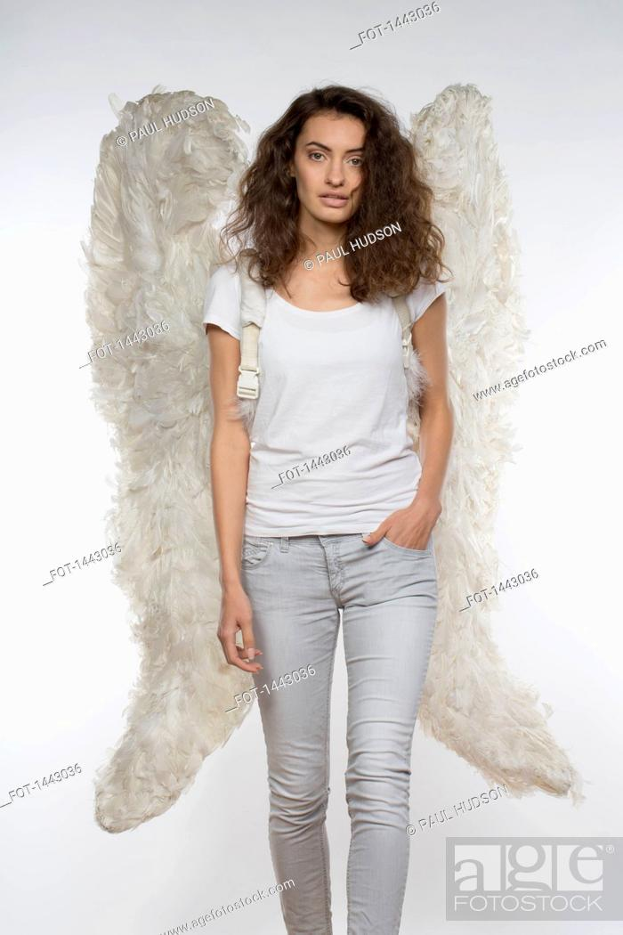 Stock Photo: Portrait of beautiful woman in angel wings walking against white background.