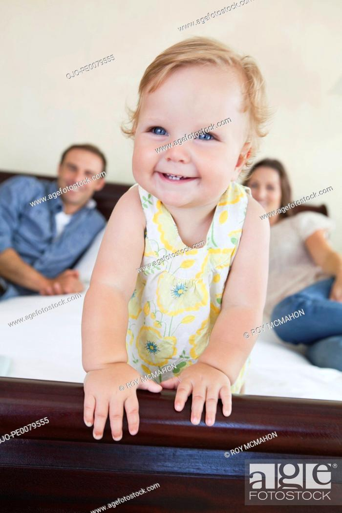 Stock Photo: Parents watching baby on bed.