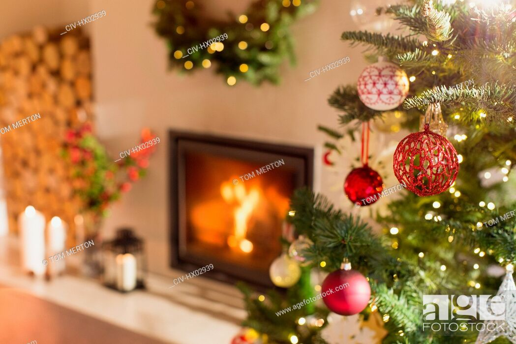 Stock Photo: Red and white ornaments hanging from Christmas tree next to fireplace.