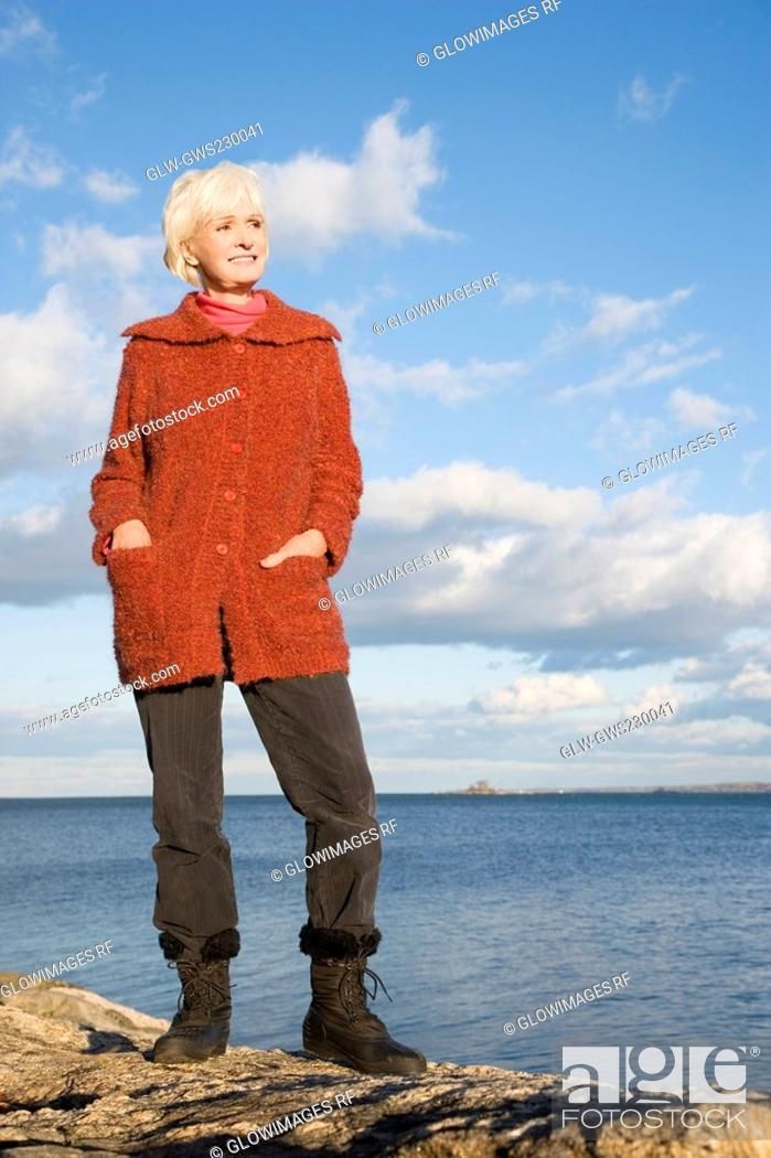 Stock Photo: Senior woman standing on a rock at seaside.