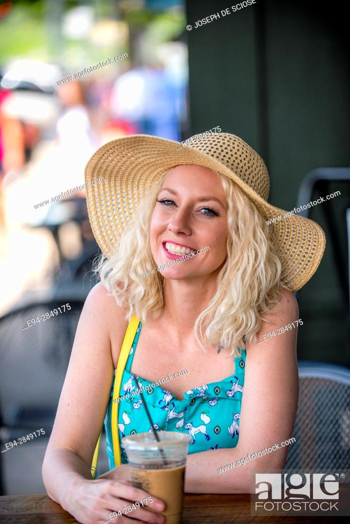 Imagen: A pretty 30 year old blond woman sitting at an outdoor cafe with a cold drink smiling at the camera.