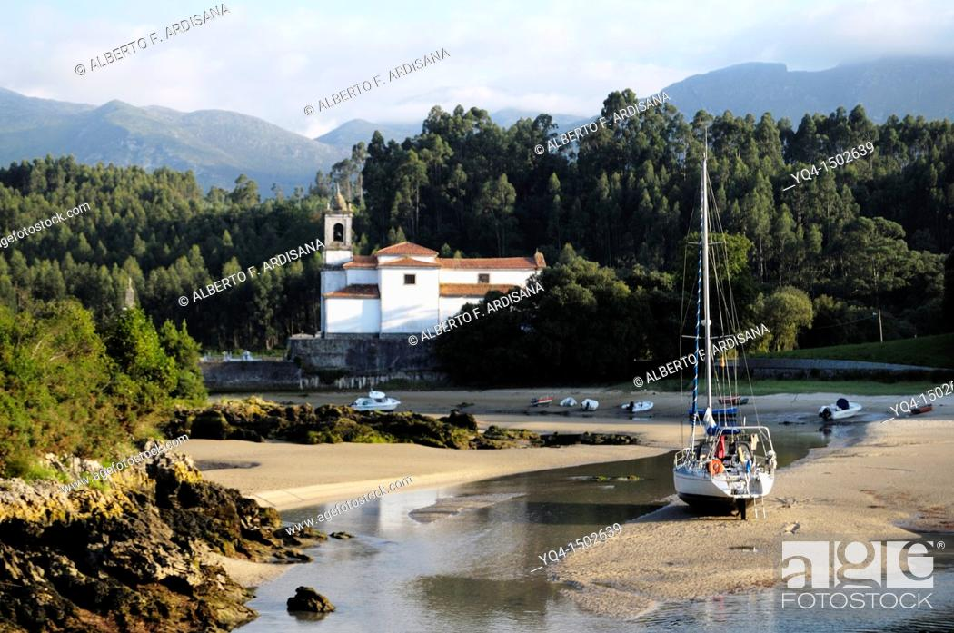 Stock Photo: View of the Ria de Niembro. A boat stranded at low tide in front of the church with the Sierra del Cuera the background. Llanes, Asturias, Spain.