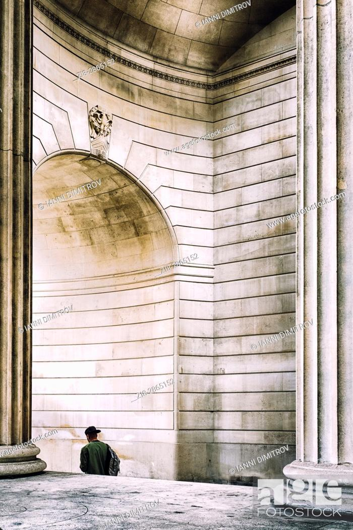 Stock Photo: Person walks under the arch of The Bank Of England , City of London, England.