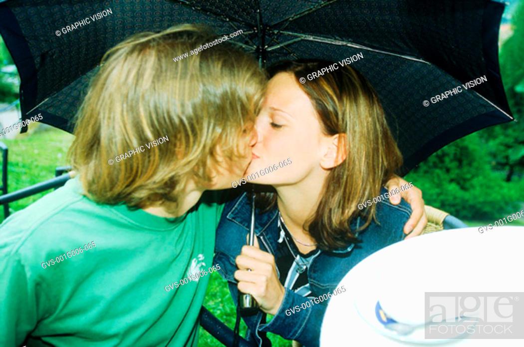 Stock Photo: Young couple kissing under an umbrella.