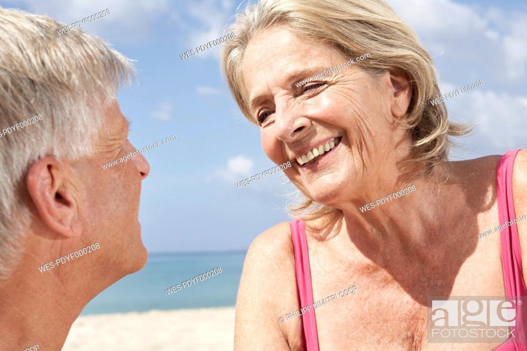 Stock Photo: Spain, Mallorca, Senior couple sitting at beach.